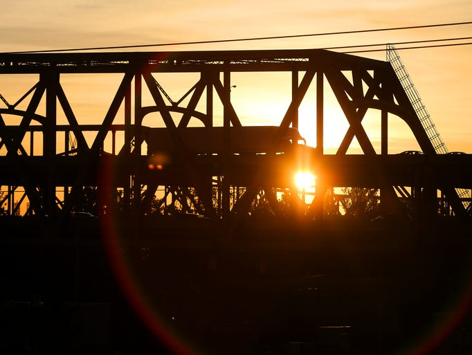 The sun rises over the Brent Suspension Bridge on Friday, May 23, 2014.