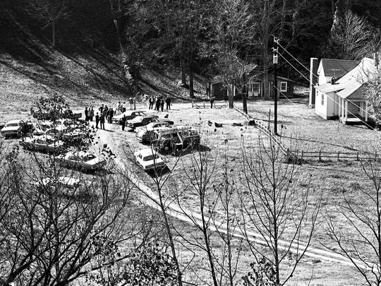Police officials and media mill around the farm Nov. 11, 1973 where David (Stringbean) Akeman, 57, and his wife, Estelle, 59, was found murdered. The couple lived in the three-room, red cottage, left of the larger, white frame house.
