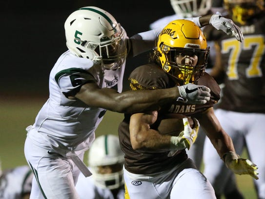 West Bloomfield's Lance Dixon tackles Rochester Adams'