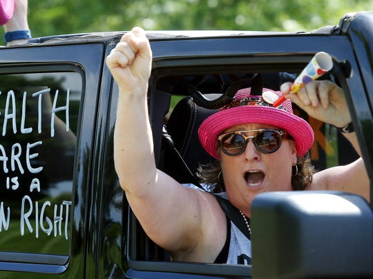 Angela Havey of Plainfield drives by as activists participate