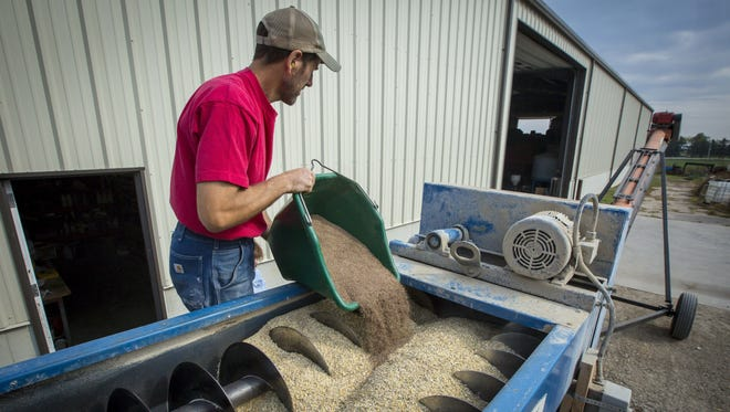 Earl Canfield mixes ingredients for horse feed at his Dunkerton farm, Monday, Oct. 2, 2017. Canfield has started growing oats, to help diversify his corn-soybean rotation, but finding he had nowhere to take the oats, decided to start mixing them as feed for cattle, horse and other small livestock producers.