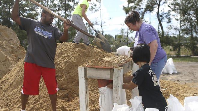 From left, Haskel Johnson, Daniel Tippett, Jennifer Tippett and Nobuko Johnson fill sand bags at the Lynn Haven Sports Complex in Lynn Haven, Fla., Monday, Oct. 8, 2018, to prepare for Hurricane Michael. (Patti Blake /News Herald via AP)