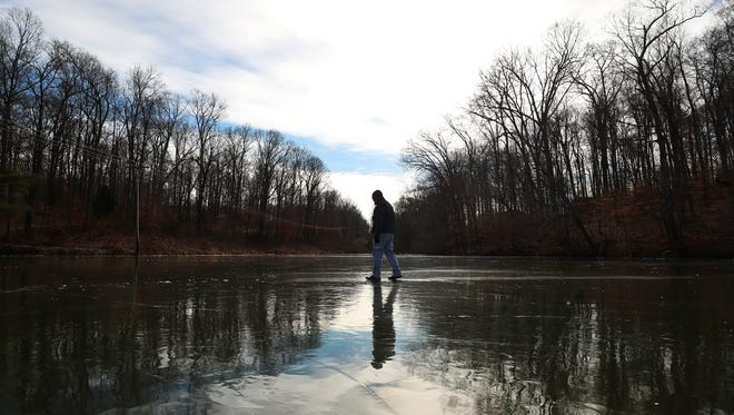 Al Papsodero walks on the frozen center of  Mount St. Francis Lake Wednesday in Floyds Knobs. Papsodero says he comes to the lake and nearby woods to relax before working at his italian restaurant in Highlander Pointe.