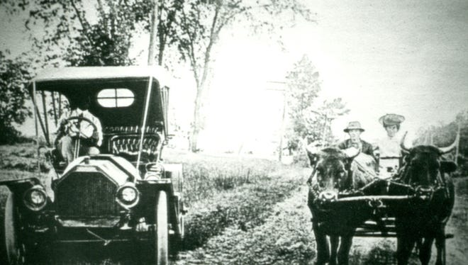 A meeting of two eras, a Ford Model T takes the edge of the road to allow a pair of oxen and their owners to pass.