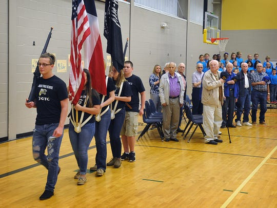 Nine veterans of the Korean War show their respect for the flag after the Rider High School JROTC color guard posted the colors Thursday morning during a ceremony honoring the vets at Jefferson Elementary. The men were granted an Honor Flight which takes them to visit war memorials in Washnigton DC.