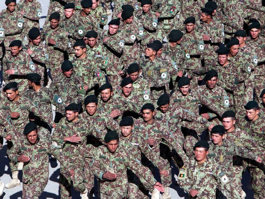 Afghan national army soldiers parade during a graduation
