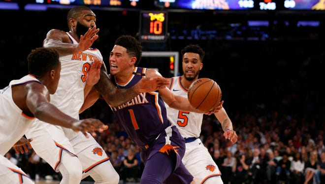 New York Knicks center Kyle O'Quinn (9) and guard Courtney Lee (5) defend against Phoenix Suns guard Devin Booker (1) during second half at Madison Square Garden.