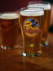 Drinks are poured in logo glasses at La Quinta Brewing