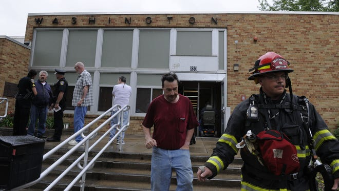 Police talk with a resident of a veterans housing building as the owner of the building and a firefighter walk out of the building.