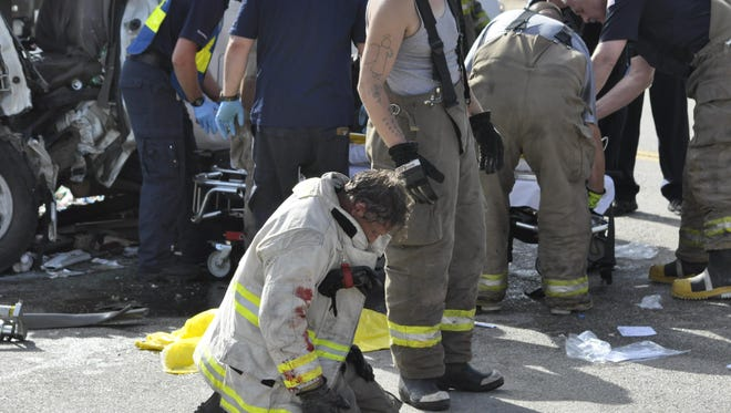 Exhausted, Cotter Fire Chief David Guist kneels and catches his breath after spending more than 40 minutes helping to stabilize an accident victim Monday morning following a collision in Gassville that left four people injured.