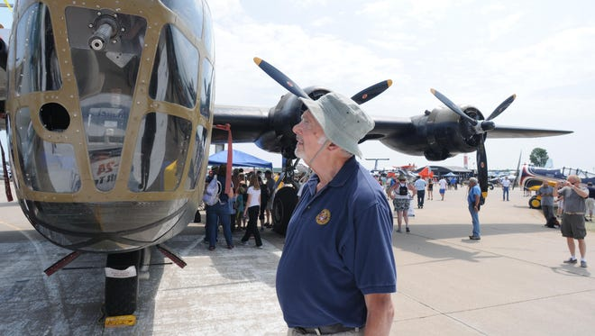 Vern Visick of Claremont, Calif., looks into the nose of the B-24 on display at the Boeing Plaza at AirVenture 2014.