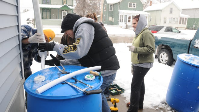 University of Wisconsin-Oshkosh students  attached a downspout diverter to a rain barrel on Frederick Street during Earth Day in 2011.
