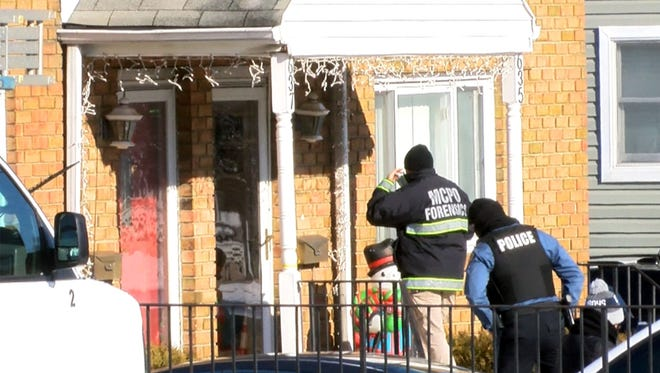 Investigators head into the Long Branch, N.J., home on Jan. 1, 2018, where three family members and a friend were shot to death just before midnight on New Year's Eve 2017.
