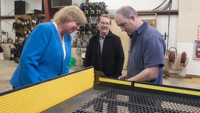 Donna Schinkle looks at some of the work being done to the wheel chair lift of a transit bus by mechanic C.J. Immel, right.