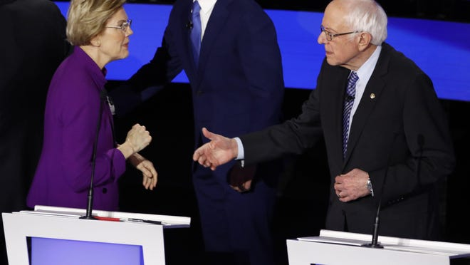 Democratic presidential candidate Sen. Elizabeth Warren, D-Mass., left and Sen. Bernie Sanders, I-Vt. talk Tuesday, Jan. 14, 2020, after a Democratic presidential primary debate hosted by CNN and the Des Moines Register in Des Moines, Iowa.