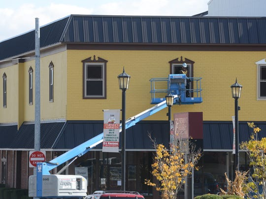Crews refurbish the windows on the second story of the Sandusky County Chamber of Commerce building on South State Street in Fremont at the end of October.