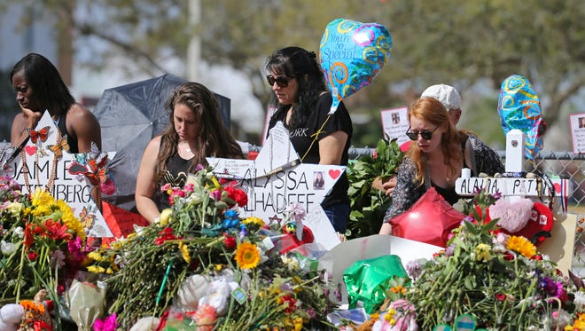 Mourners bring flowers as they pay tribute at a memorial for the victims of the shooting at Marjory Stoneman Douglas High School Feb. 25, 2018, in Parkland, Fla.