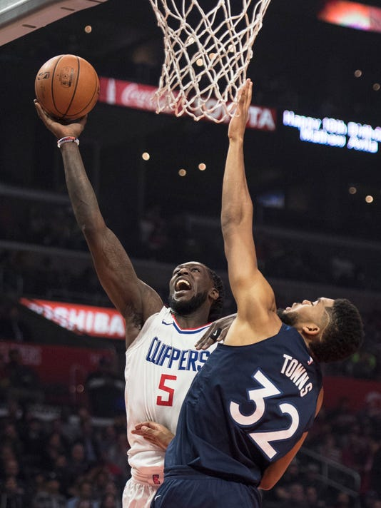 Los Angeles Clippers forward Montrezl Harrell, left, shoots under pressure as Minnesota Timberwolves center Karl-Anthony Towns defends during the first half of an NBA basketball game on Wednesday, Dec. 6, 2017, in Los Angeles. (AP Photo/Kyusung Gong)