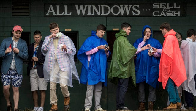 Infield attendees seek cover under a betting window awning from the rain during the 2017 Oaks.
