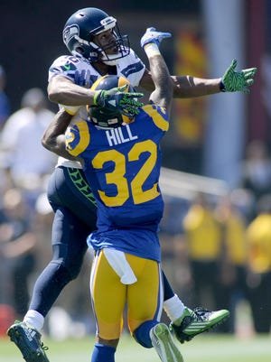 Rams cornerback Troy Hill tries to break up a pass intended for Seahawks receiver Tyler Lockett during the third quarter of Sunday's game at the Coliseum.
