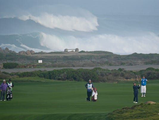 Scott Brown, right, follows his shot from the 10th fairway of the Monterey Peninsula Country Club Shore Course, with large waves in the background, during the second round of the AT&T Pebble Beach National Pro-Am golf tournament Friday, Feb. 12, 2016, in Pebble Beach, Calif. At left is Brown's playing partner Colt Ford. (AP Photo/Eric Risberg)