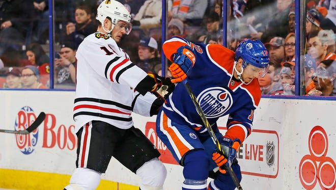 Edmonton Oilers forward Rob Klinkhammer (12) and Chicago Blackhawks forward Bryan Bickell (29) battle for a puck behind the Chicago net during the second period at Rexall Place.