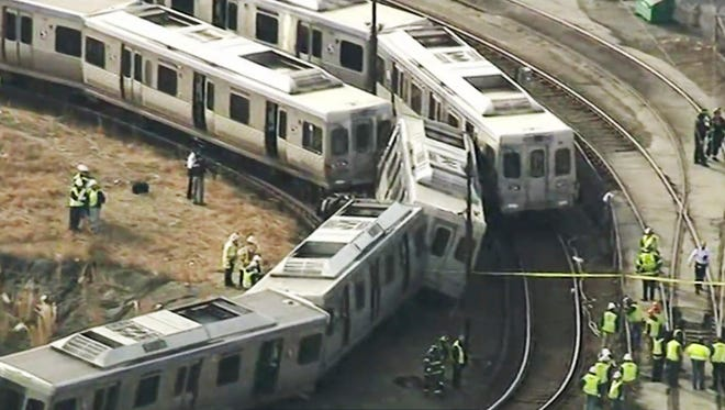 In this image from video provided by WPVI, officials investigate an accident involving out-of-service commuter trains in Upper Darby, Pennsylvania, Tuesday.