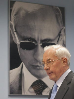 Former Ukrainian prime minister Mykola Azarov walks in front of a photograph of Russian President Vladimir Putin on Wednesday in Moscow.