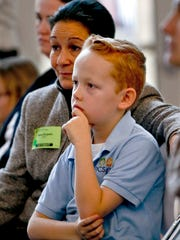 Nine-year-old Collinson Burgwin sits with his mother Maria as he listens to speakers talk about the Children's Health Insurance Program, CHIP, during a news conference, Dec. 7, 2017, in Pittsburgh. The gathering marked the 25th anniversary of the Pennsylvania program to provide health insurance to uninsured children and teens who are not eligible for or enrolled in Medical Assistance. Miller, local health care providers, and families with children using CHIP spoke to call on Congress to reauthorize the program for children who rely on the health care coverage. (AP Photo/Keith Srakocic)
