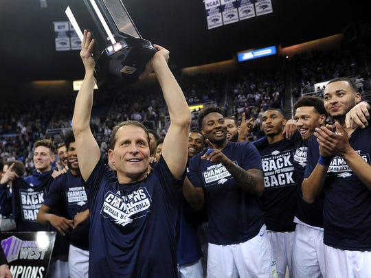 Nevada head coach Eric Musselman hoists the MW regular-season championship trophy after a win over Colorado State last month.