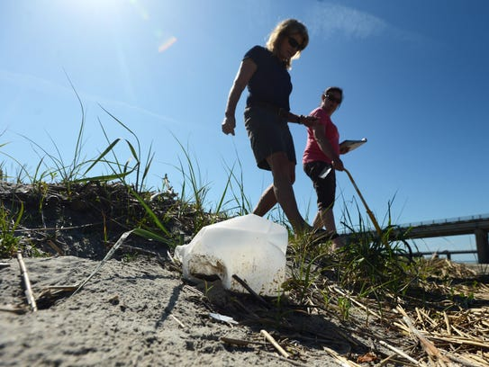 Kathy O'Hara, left, scans the beach for litter while