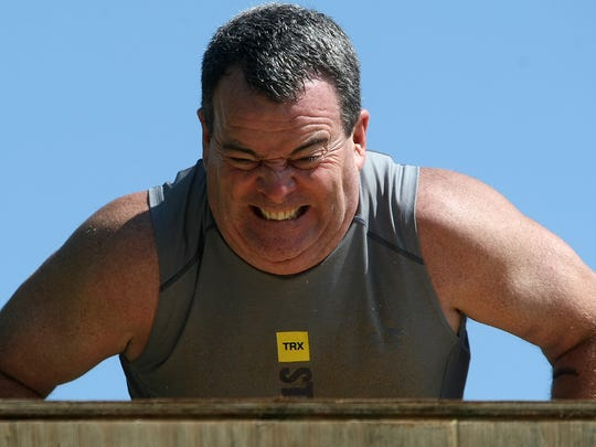Retired United States Army Lt. Col. Stan Fugate pulls himself on to the top of the ninja wall during the inaugural Chief's Challenge at Fairgrounds Park on Saturday, April 23, 2016.
