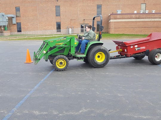 Michaela Shorb, of Fairfield, demonstrates her tractor driving technique driving through the gate after completing the serpentine driving course for the Safe Tractor and Machinery program.