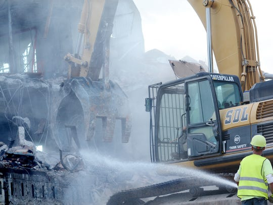 A worker sprays the site as crews bring down the former