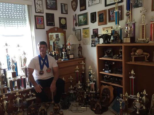 Pensacola's Larry Tilley, 65, at his home with 93 medals, trophies or plaques he has attained in competitive powerlifting competition. He set an American record in the Masters division for a squat lift at recent competition in Orange Beach.