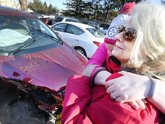 Maureen Fromm, right, is hugged by her daughter Kelly at Beard's Towing in Jacobus Tuesday January 31, 2017. Maureen said that the 2015 Ford Escape, in the background, that she was traveling with her husband Dean was lodged beneath the tractor trailer where the driver died during the 50 vehicle pileup on Interstate 83 Monday.