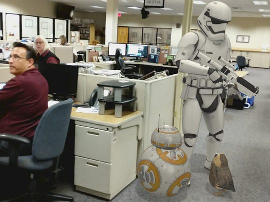 A Storm trooper, BB-8, and a Porg stand behind news director, Randy Parker in the York Daily Record newsroom. The Star Wars Google AR stickers interact with each other.