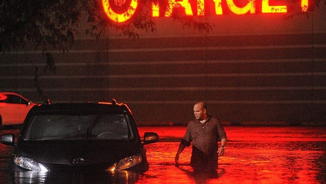 A man looks into a flooded car while wading through high water at 43rd Street and Kelley Avenue near the Louise Avenue Target store after heavy rains Aug. 27.