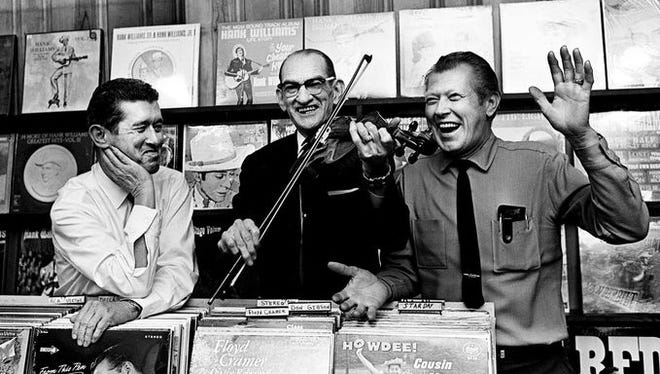 """Roy Acuff, left, and Pete """"Brother Oswald"""" Kirby, right, have fun with Fiddlin' Sid Harkreader as they greet disc jockeys and fans at Ernest Tubb Record Shop Oct. 20, 1965. Everyone is arriving into Nashville for the D.J. Convention and Grand Ole Opry's 40th birthday party."""