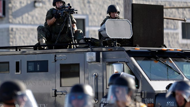 FILE - In this Aug. 9, 2014, file photo, a police tactical team moves in to disperse a group of protesters following the shooting of a young black man by a white policeman in Ferguson, Mo. Since then, legislators in almost every state have proposed changes to the way police interact with the public including measures addressing limits on the flow of surplus military equipment. (AP Photo/Jeff Roberson, File)