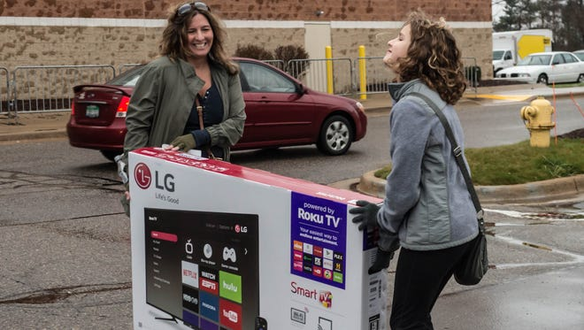 Battle Creek residents Kathy Yoder and Annika Yoder, 10, haul a new 55-inch television from Best Buy to their vehicle on Friday