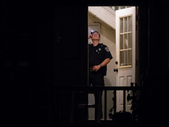 A Rochester Police Officer investigates a house on Garson Ave. where a caller was transported to the hospital after being shot at a house party on Woodward St. early in the morning on Saturday, September 12, 2015. The shooting left two dead and four injured.