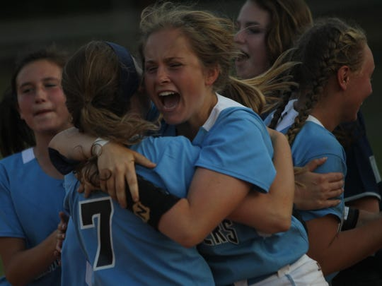 Left: Maclay's Keegan Cardman jumps into the arms of teammate Olivia Borschel to celebrate the Marauders' 9-7 win over NFC in eight innings to earn a district title.