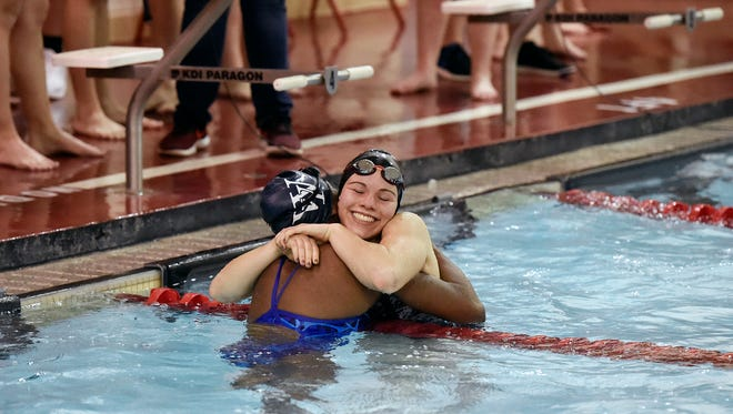 West York's Tesia Thomas and Dover's Grace Beierschmitt embrace after completeing the girls' 200-yard freestyle relay in a YAIAA dual swim meet Thursday, Jan. 11, 2018, at Dover. Dover swept West York, with the girls winning 101-83 and boys winning 90-88. Beierschmitt's relay team won the event with a time of 1:48.45.