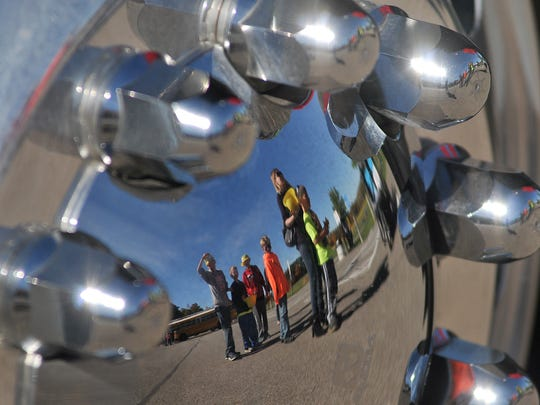 Children reflected in a rim wait in line to climb a