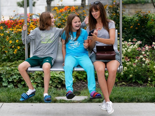 From left: Emma, 9, Rosa, 7, and Christa Lloyd, sit