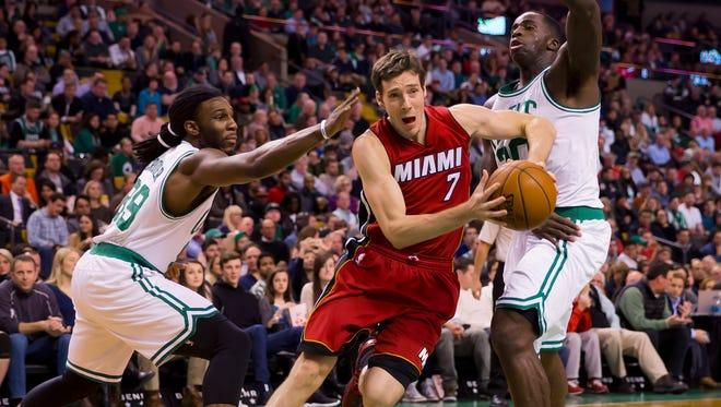 Miami Heat guard Goran Dragic drives between Boston Celtics forwards Jae Crowder and Brandon Bass at TD Garden.