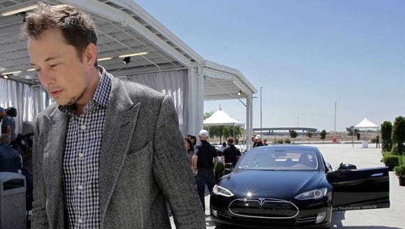 In a 2012 file photo, Tesla CEO Elon Musk walks past