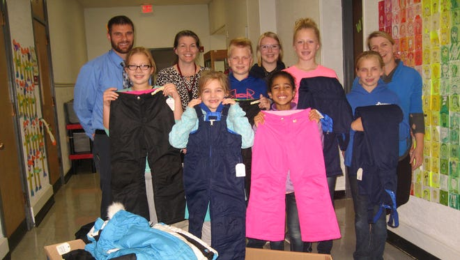 A group of Northern Cloverleaf 4-H members present snowpants and winter boots to Mr. Baier at Sevastopol School.