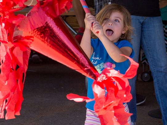 Valerie Flora swings at the piñata at the annual Día